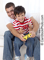Smiling father and kid playing video games at home