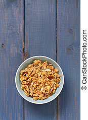 granola in blue bowl on blue background