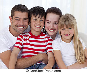 Portrait of family sitting on sofa together - Portrait of...