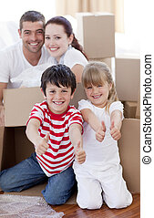 Family moving house with boxes and thumbs up - Happy family...