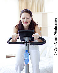 Woman doing spinning bike at home - Woman doing spinning...