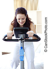 Beautiful woman doing spinning at home - Beautiful woman...