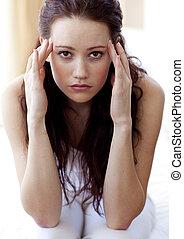 Brunette woman having a headache in bed