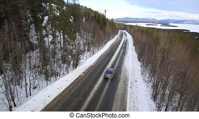 the car rides on a winter road among the woods and mountains