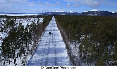 the car rides on a winter road among the woods and mountains...