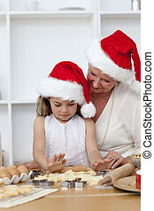 Grandmother and grandaughter baking Christmas cakes -...