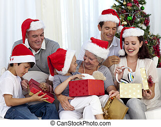 Family opening Christmas presents at home