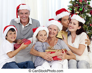 Family giving presents for Christmas - Family in sofa giving...