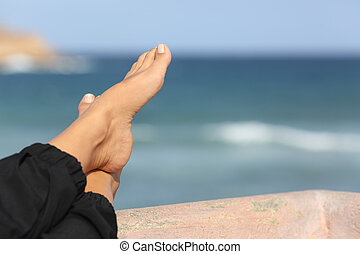 Woman feet relaxing on an hotel beach terrace - Close up of...