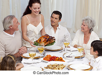 Woman showing turkey to her family for Christmas dinner at...