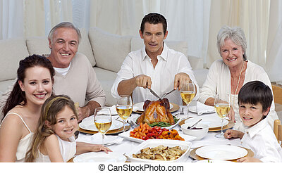 Family eating turkey and vegetables in a celebration meal at...