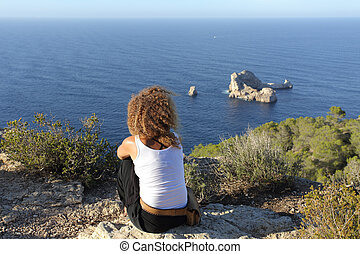 Woman pensive relaxing on a cliff in Ibiza island - Seascape...
