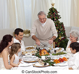 Grandfather cutting the family turkey in Christmas dinner