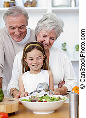 Happy grandparents eating a salad with granddaughter in the...