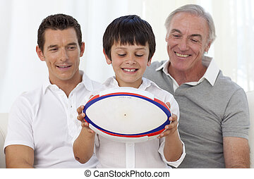 Son holding a rugby ball with his father and grandfather on...