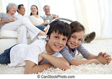 Children on floor listening to the music in living-room -...