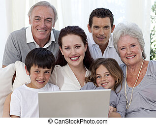 Portrait of family sitting on sofa using a laptop