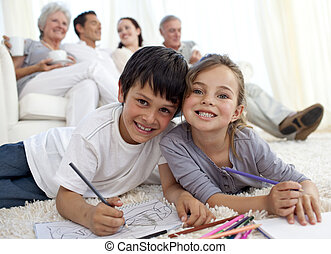 Children painting on floor with their family in sofa at home