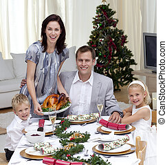 Parents and children celebrating Christmas dinner with...
