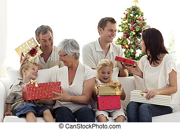 Happy family at home opening Christmas presents