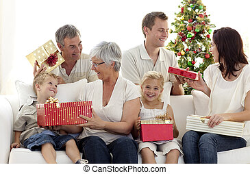 Family sitting on sofa delivering Christmas presents