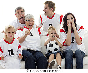 Family watching a football match in television at home