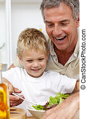 Happy grandfather eating a salad with grandson