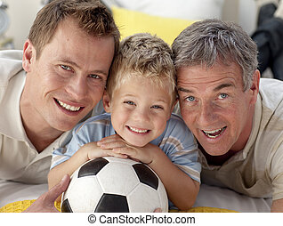 Portrait of smiling son, father and grandfather on floor -...