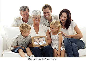 Happy family holding a portrait of children sitting on sofa