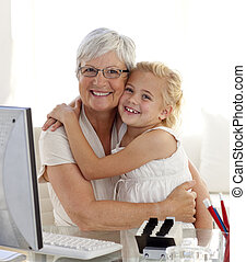 Granddaughter and grandmother hugging and using a computer...