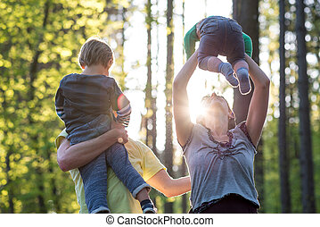 Parents playing with their two young children outdoors in a...