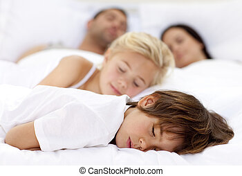 Children sleeping with his parents in a big bed