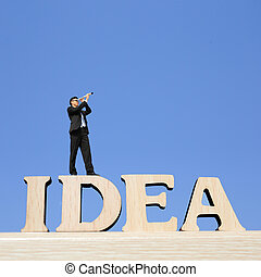 Idea - business man stand on Idea text word with telescope...