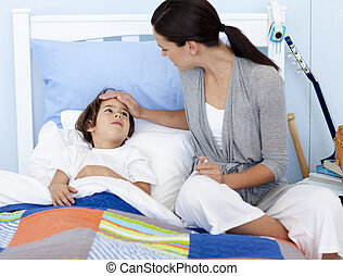 Mother taking her sons temperature lying in bed