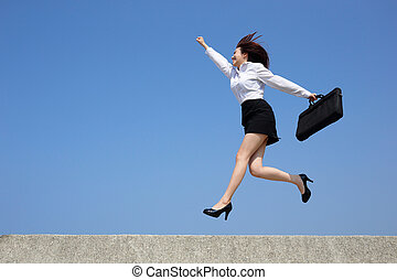 Successful business woman jump and run with blue sky...