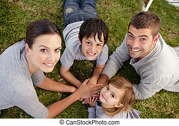 Parents and kid lying on garden with hands together -...
