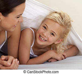 Mother and daughter playing under the bedsheets - Mother and...