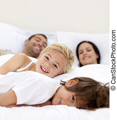 Family realxing in parent\'s bed