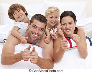 Family lying on parent\'s bed with thumbs up