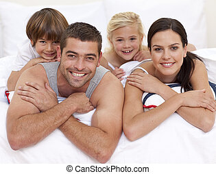Happy family playing in parent\'s bed