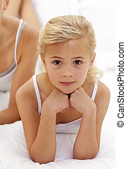 Portrait of a little girl lying on bed - Portrait of serious...