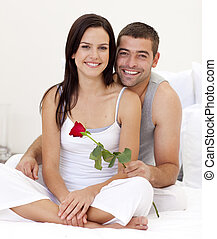 Couple sitting on bed with a rose