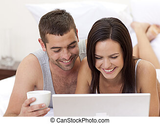 Couple in bed having fun with a laptop