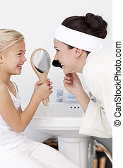 Little girl holding a mirror and mother putting makeup in...