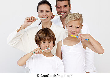 Portrait of family cleaning their teeth in bathroom -...