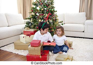 Siblings opening gifts in the living-room - Happy siblings...