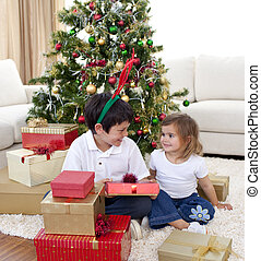 Siblings opening gifts in front of christmas tree - Happy...