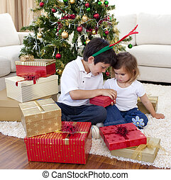 Smiling brother and sister looking at Christmas gifts