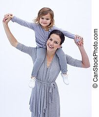Mother giving her daughter piggyback ride against white -...