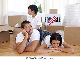 Tired family relaxing on floor after buying new house -...